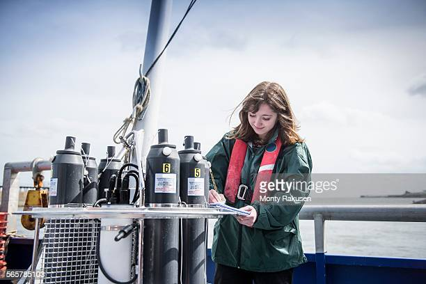 Female scientist making notes with sea water sampling experiment on research ship