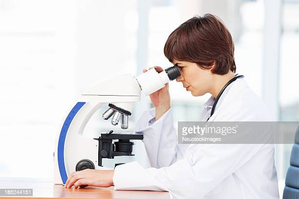 Female Scientist Reviewing Specimen On Microscope