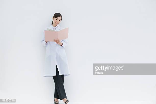 Female scientist standing and looking at file