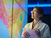 Female scientist with silicon wafer studying graphical display of wafer on screens