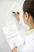 Female scientist writing down molecular structure on whiteboard, rear view, differential focus