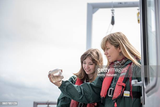 Female scientists inspecting sample of plankton on research ship