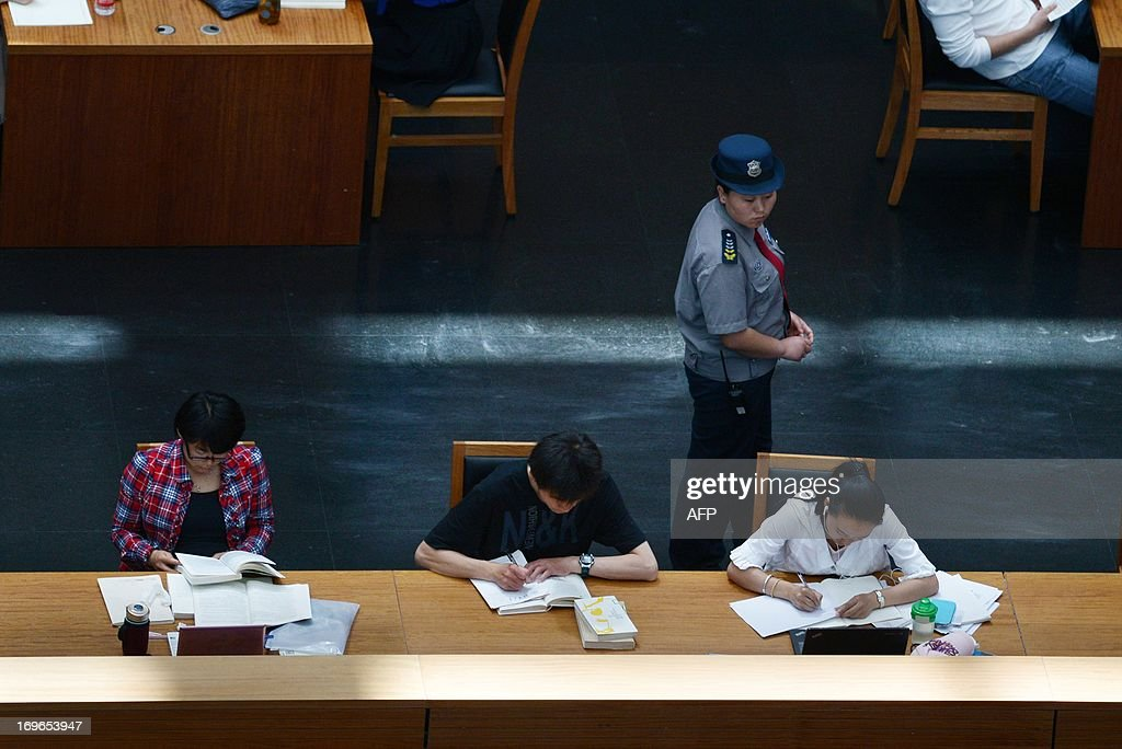 A female security guard (2nd R) walks as people read books at a national library in Beijing on May 30, 2013. China's ruling Communist Party has called for greater political instruction for young university teachers, the education ministry has said. AFP PHOTO/WANG ZHAO
