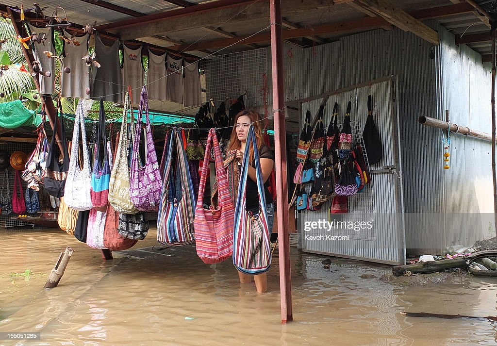A female sells Thai handicraft displayed outside her shop situated on the water in floating market on October 14 in Damnoen Saduak, Thailand. Damnoen Saduak is a district in the province of Ratchaburi in central Thailand. The central town has become a tourist attraction with its famous floating market.