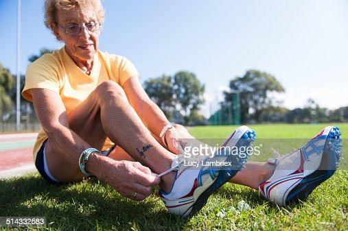 Female senior athlete (75) lacing spiked shoes : Stockfoto