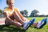 Female senior athlete (75) lacing spiked shoes