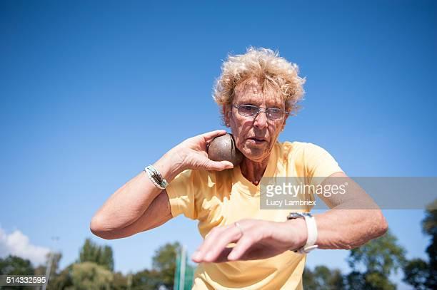 Female senior athlete (75) practicing shot put
