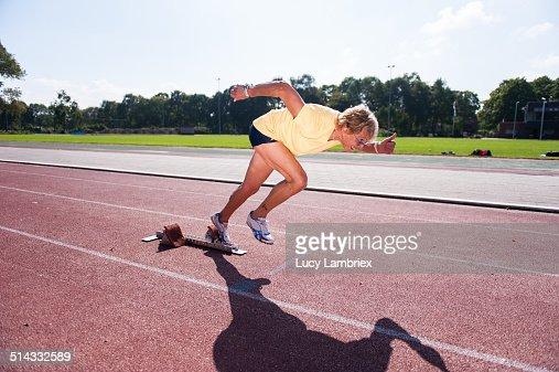 Female senior athlete (75) taking off for a sprint : Stockfoto