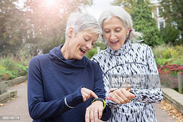 Female senior joggers checking fitness watches.