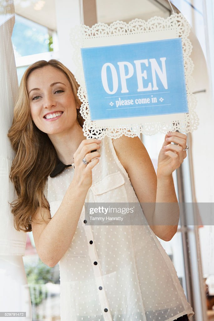 Female setting open sign in store window : Stock Photo