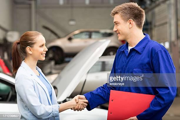 Weibliche schütteln Hände mit Auto-Mechaniker