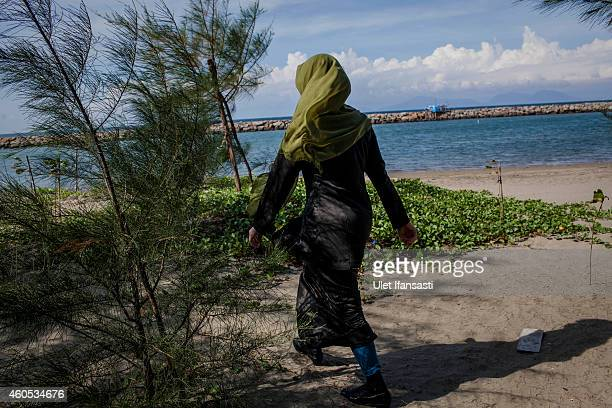 A female sharia police known as Wilayatul Hisbah walks in beach as they patrol on December 12 2014 in Banda Aceh Indonesia Aceh is the only province...