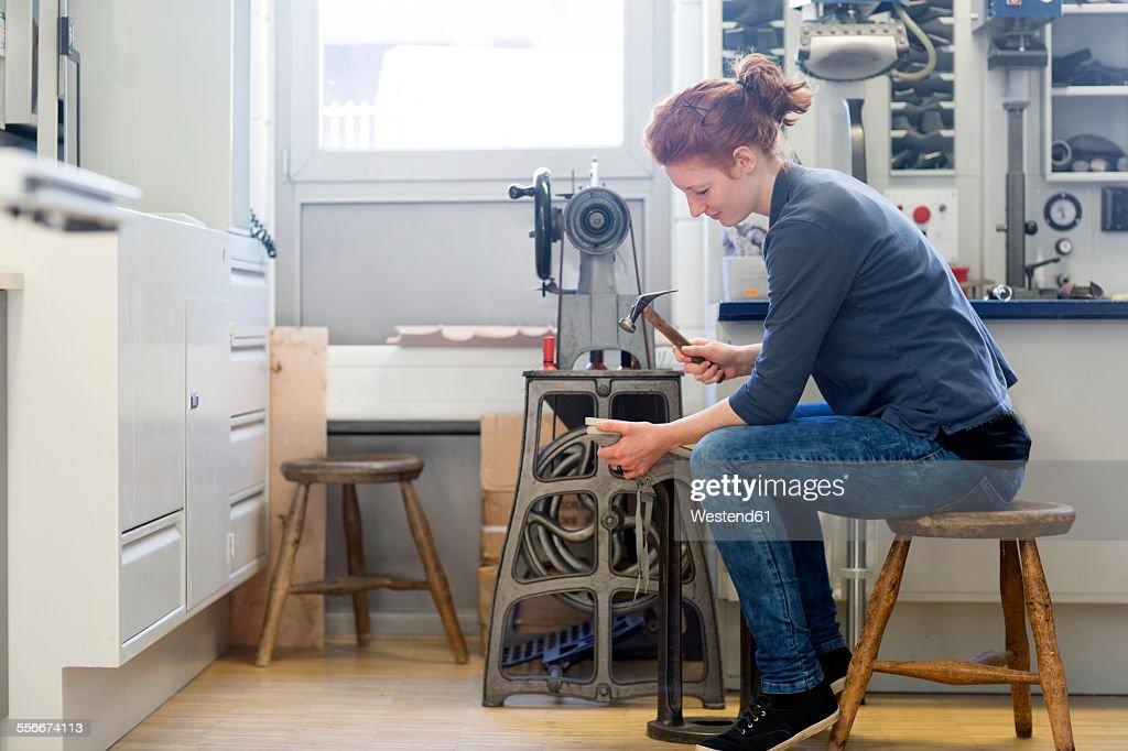 Female shoemaker preparing shoe with a hammer