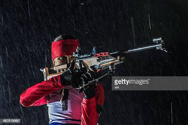 Female shooting at biathlon training at night