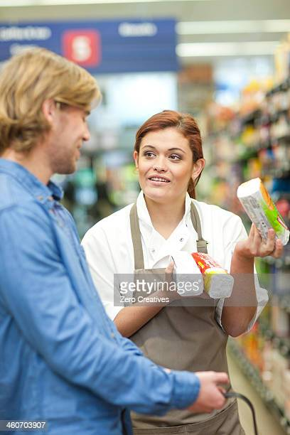 Female shop assistant advising male customer
