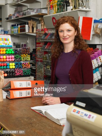 Female shop assistant behind counter in stationery shop, portrait