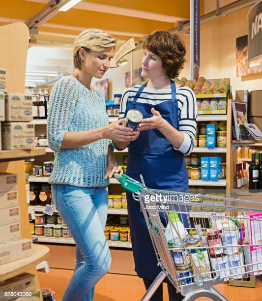 female shop assistant explaining woman product in store
