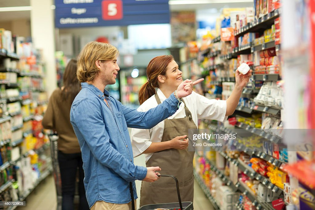 Female shop assistant guiding male customer : Stock Photo
