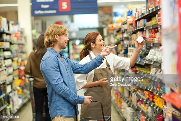 Female shop assistant guiding male customer