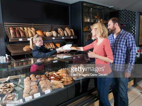 Female shop assistant in a bakery serving customers