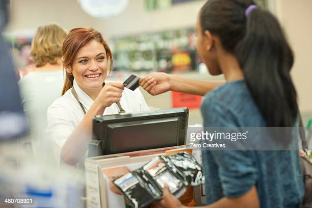 Female shop assistant receiving card from customer