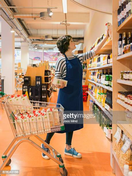 female shop assistant stacking shelves in supermarket