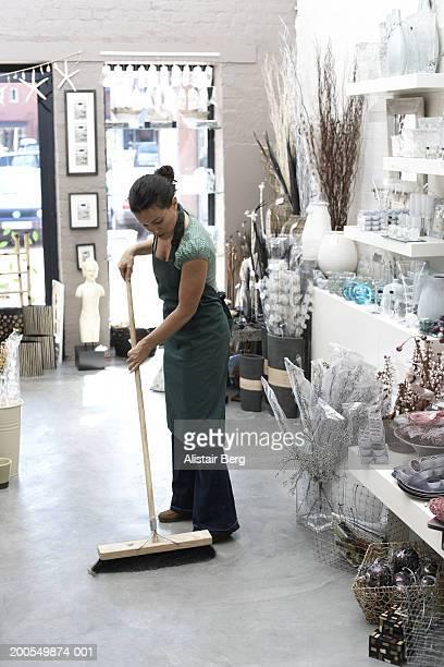 Female shop assistant sweeping floor in interior design shop