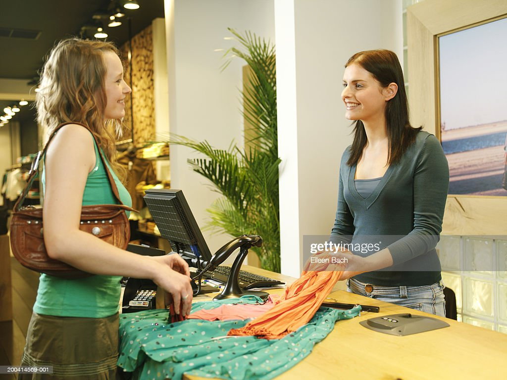 female shop assistant taking clothes from w  at counter smiling    female shop assistant taking clothes from w  at counter  smiling   stock photo