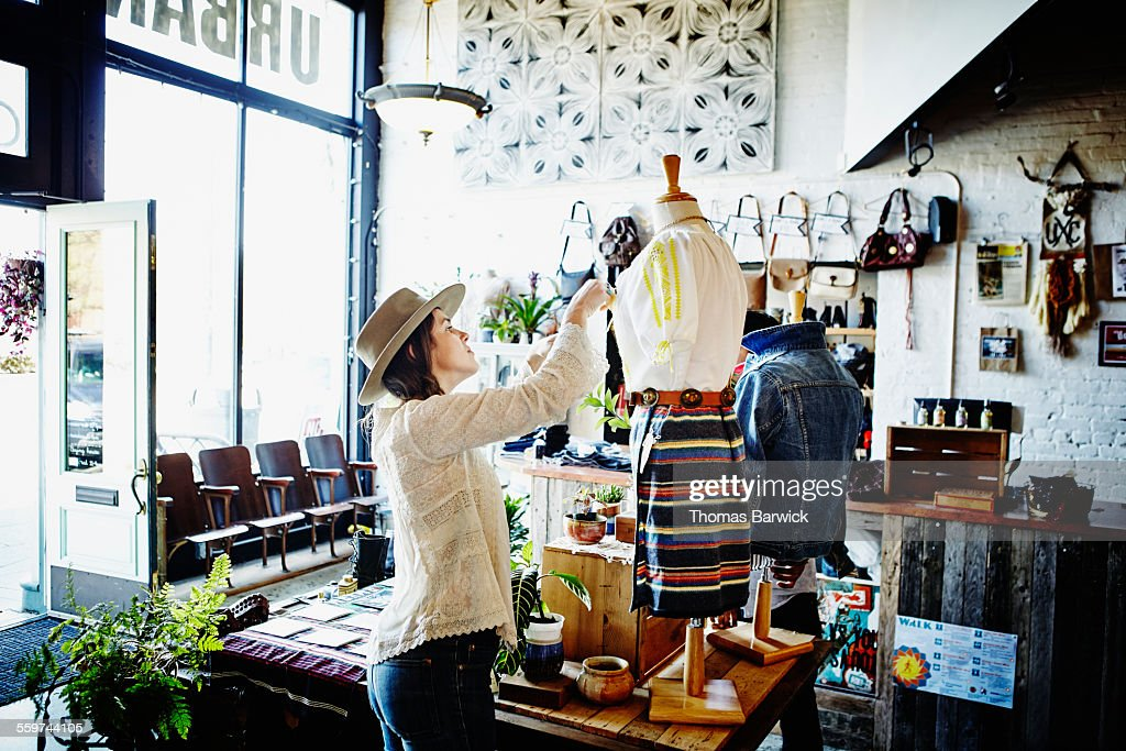 Female shop owner dressing mannequin for display : Stock Photo