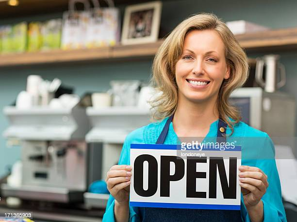 Female Shop Owner Holding an Open Signboard