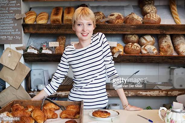 Female shopkeeper behind counter in bakery.