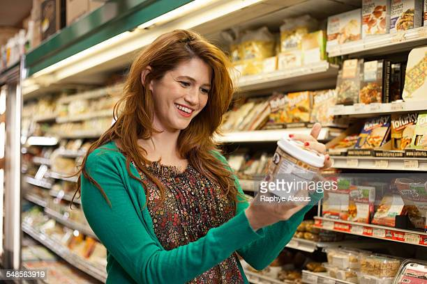 Female shopper checking product in health food store