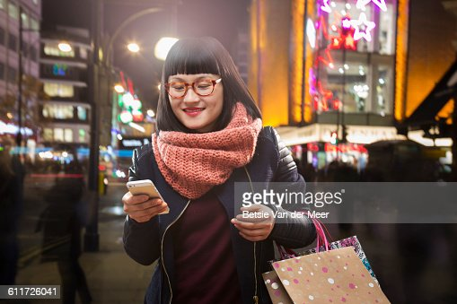 female shopper looks at digital device in city.