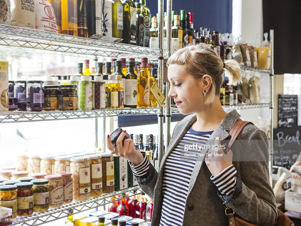 Female shopper reads label of jar in shop.
