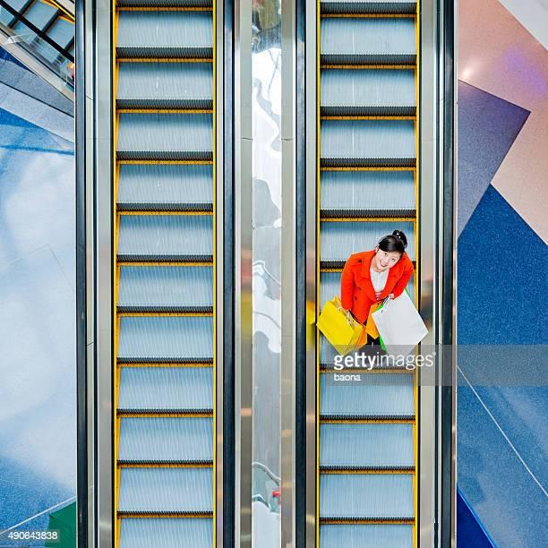 Female shopper standing on escalator