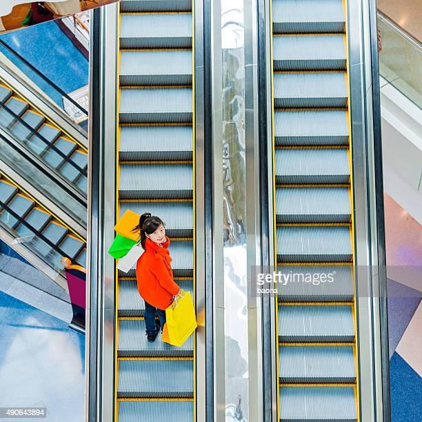 Weibliche shopper auf Rolltreppe