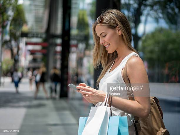Female shopper texting on her phone