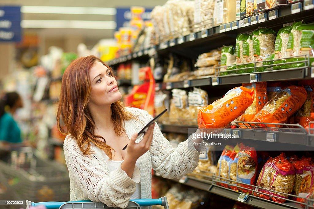 Female shopper with digital tablet in supermarket