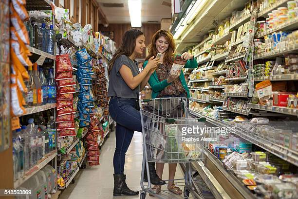 Female shoppers checking products on smartphone in health food store