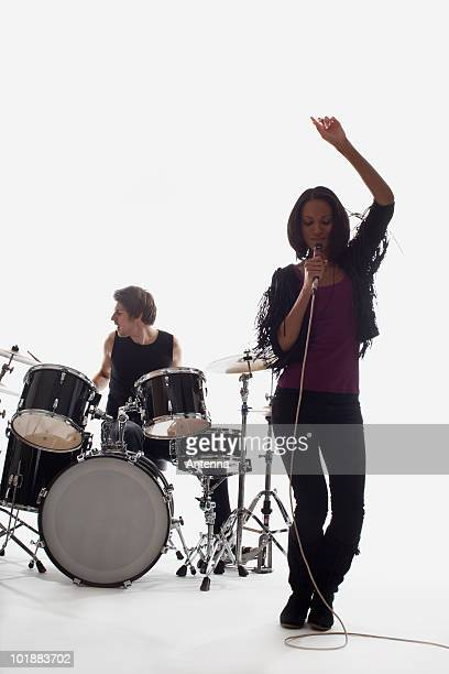 A female singer and a drummer performing, studio shot, white background, back lit