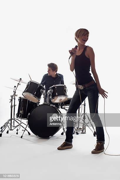 A female singer and a man on drums performing, studio shot, white background, back lit