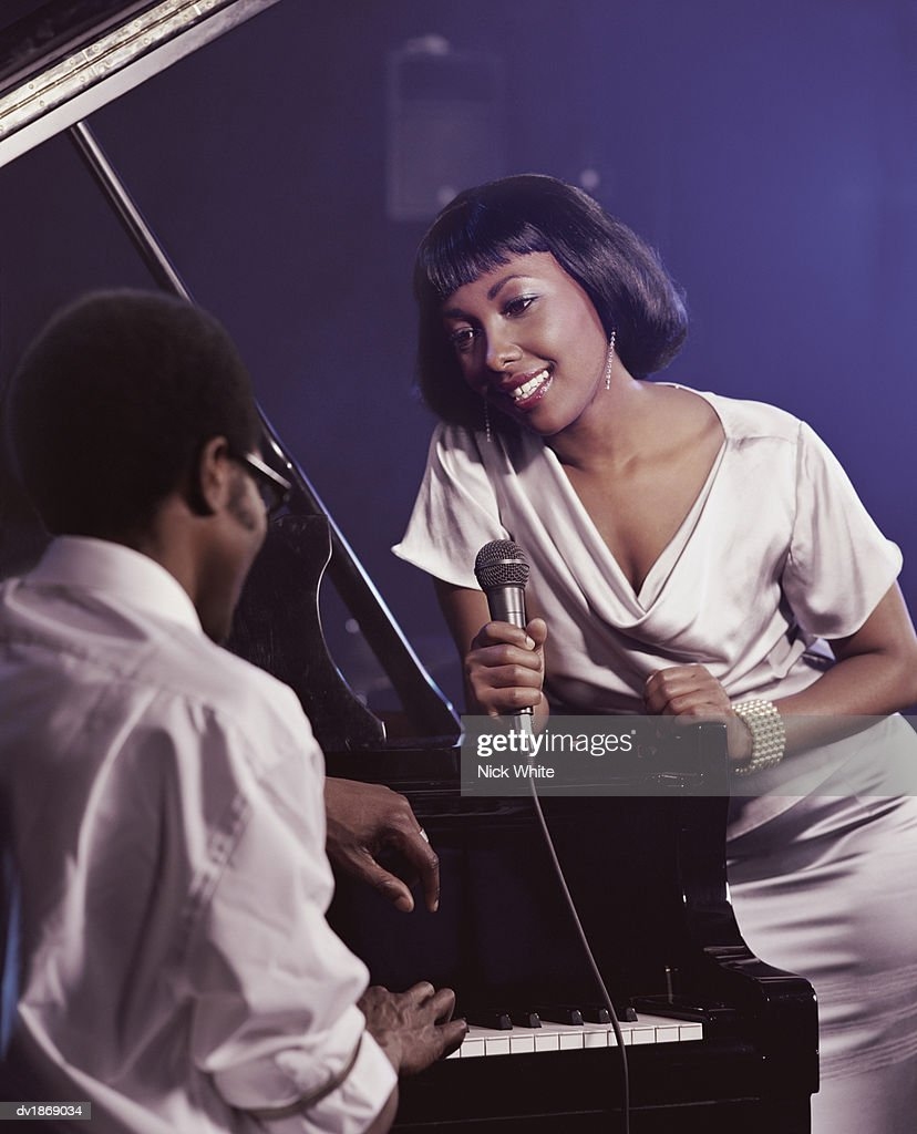 Female Singer in a Nightclub Holding a Microphone and Singing to a Pianist : Stock Photo