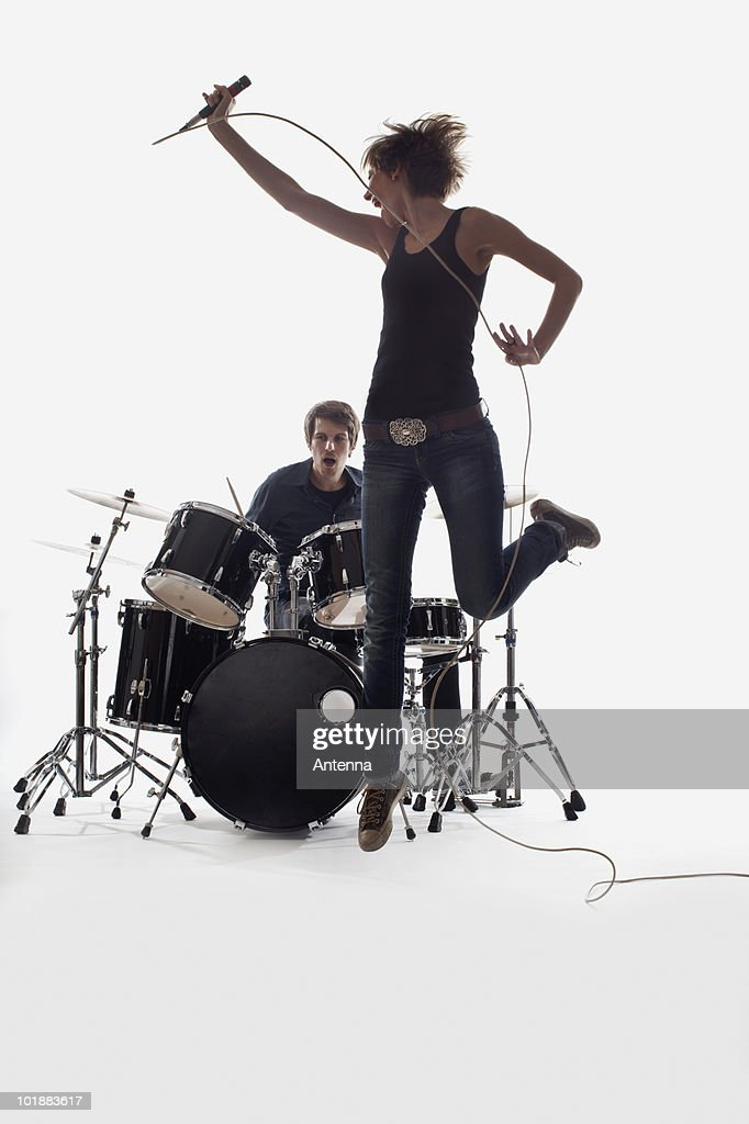 A female singer jumping and a man on the drums performing, studio shot, white background, back lit