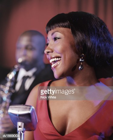Female Singer on Stage Singing into a Microphone and a Man in the Background Playing a Saxophone : Stock Photo