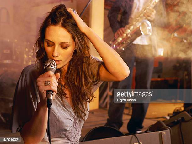 Female Singer Performing on Stage With a Man in the Background Playing a Saxophone