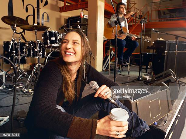 Female Singer Sits on a Stage Having a Coffee Break at a Gig Rehearsal