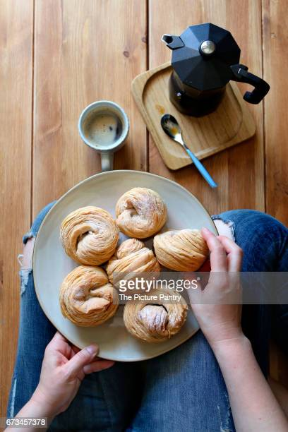 Female sitting on the floor and having  breakfast with cruffin pastry and a cup of coffee.Top view