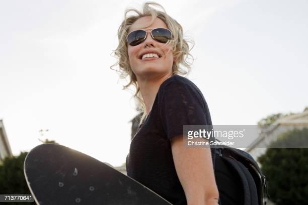 Female skateboarder carrying skateboard in park