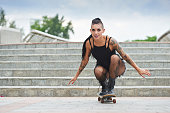 Stylish young woman with tattoo skateboarding