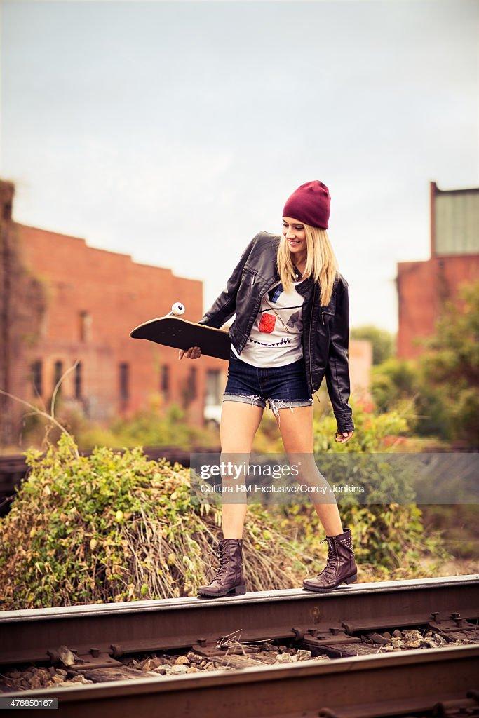 Female skater walking along railway track